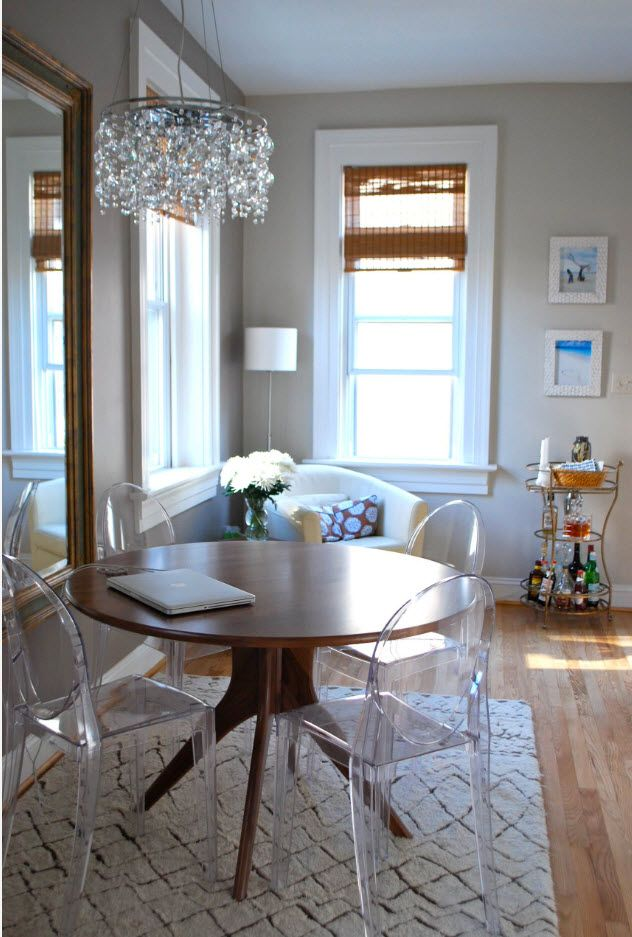 Plexiglass chair and round wooden table in the classic dining room