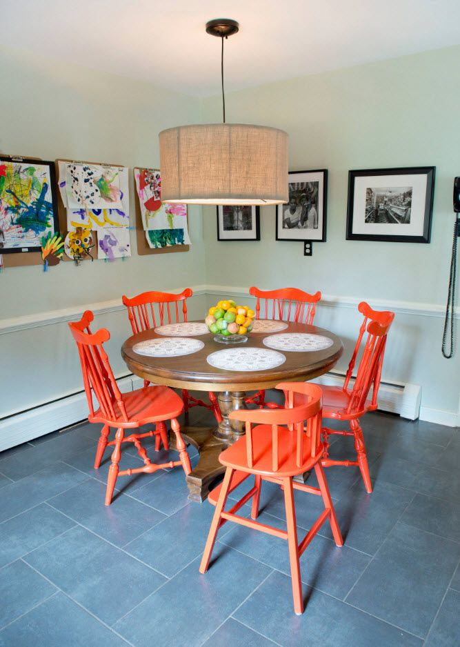 Orange chairs in the small dining zone in the apartment decorated with small pictures