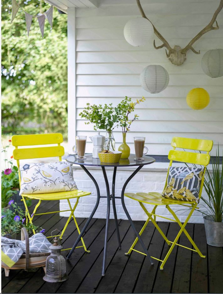 Causal style of the porch with coffe table for two and two yellow tables