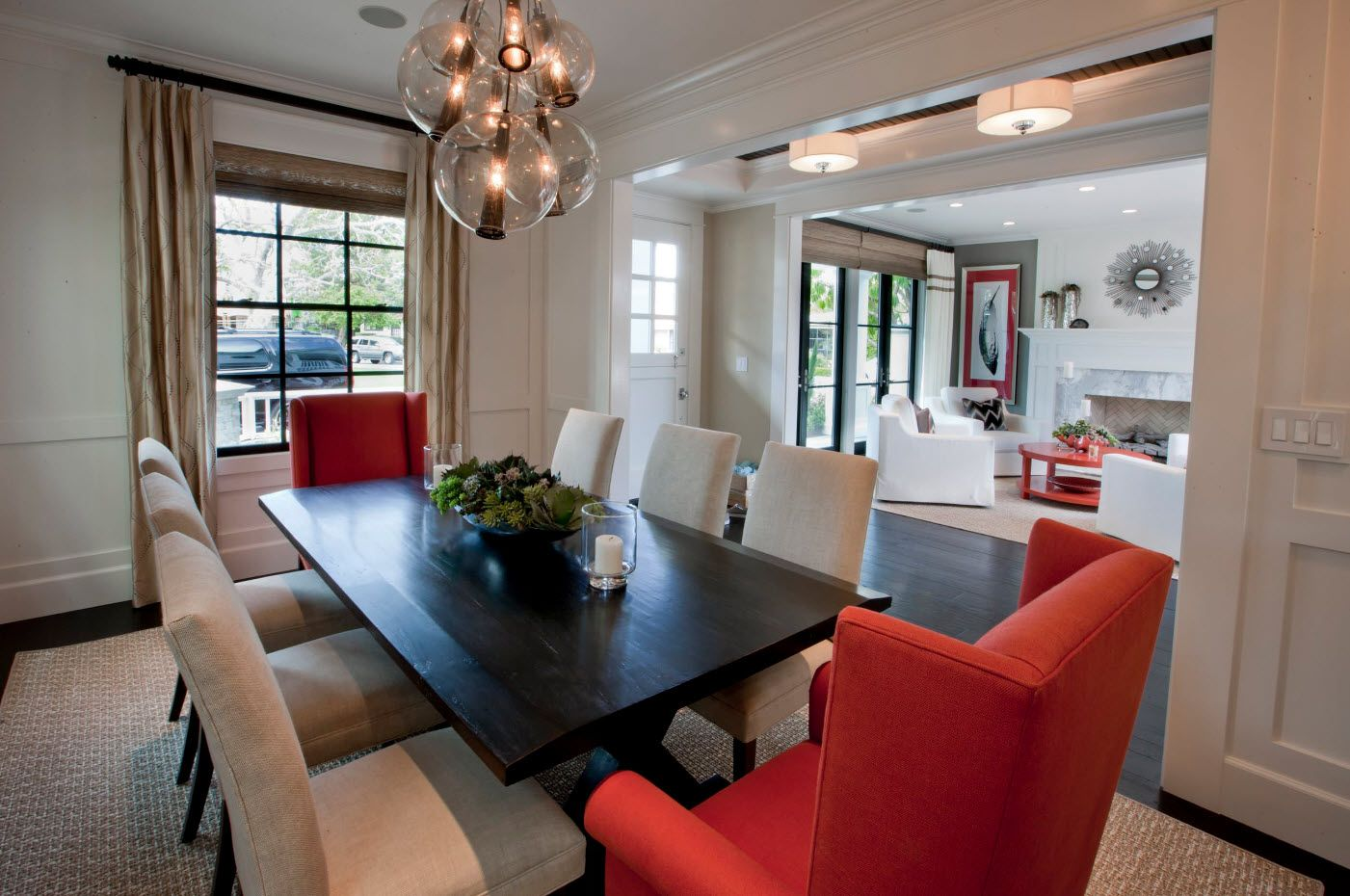 Red armchairs, gray sofa and black table for the accentual filling of the dining room