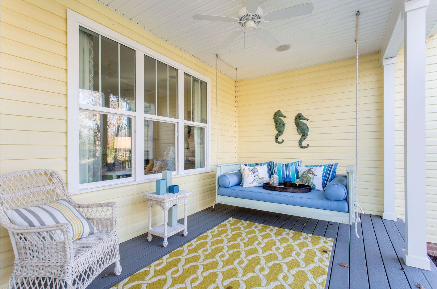 Pale yellow wooden panelling of the house's facade and a rug at the wooden platform of the furnished porch