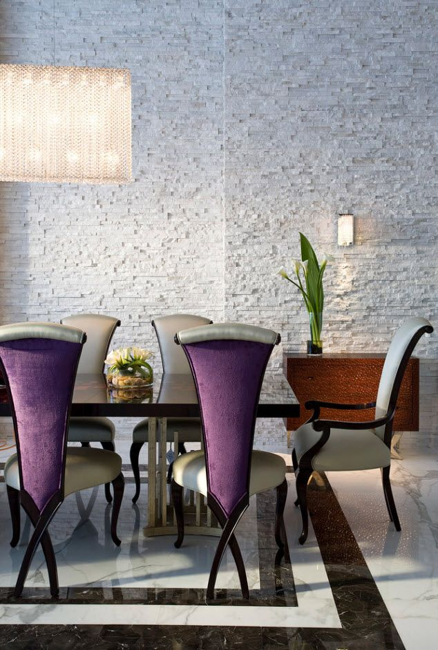 velvet chairs of unusual form in the wallpapered dining room