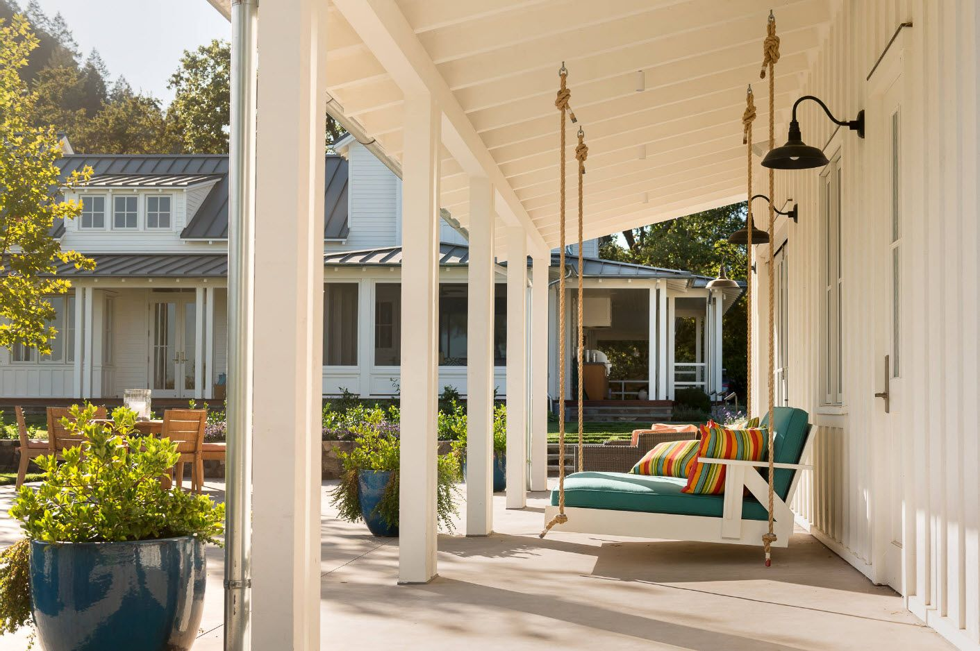 Nice white wooden trimmed porch with rope swing bed to nap at the nature