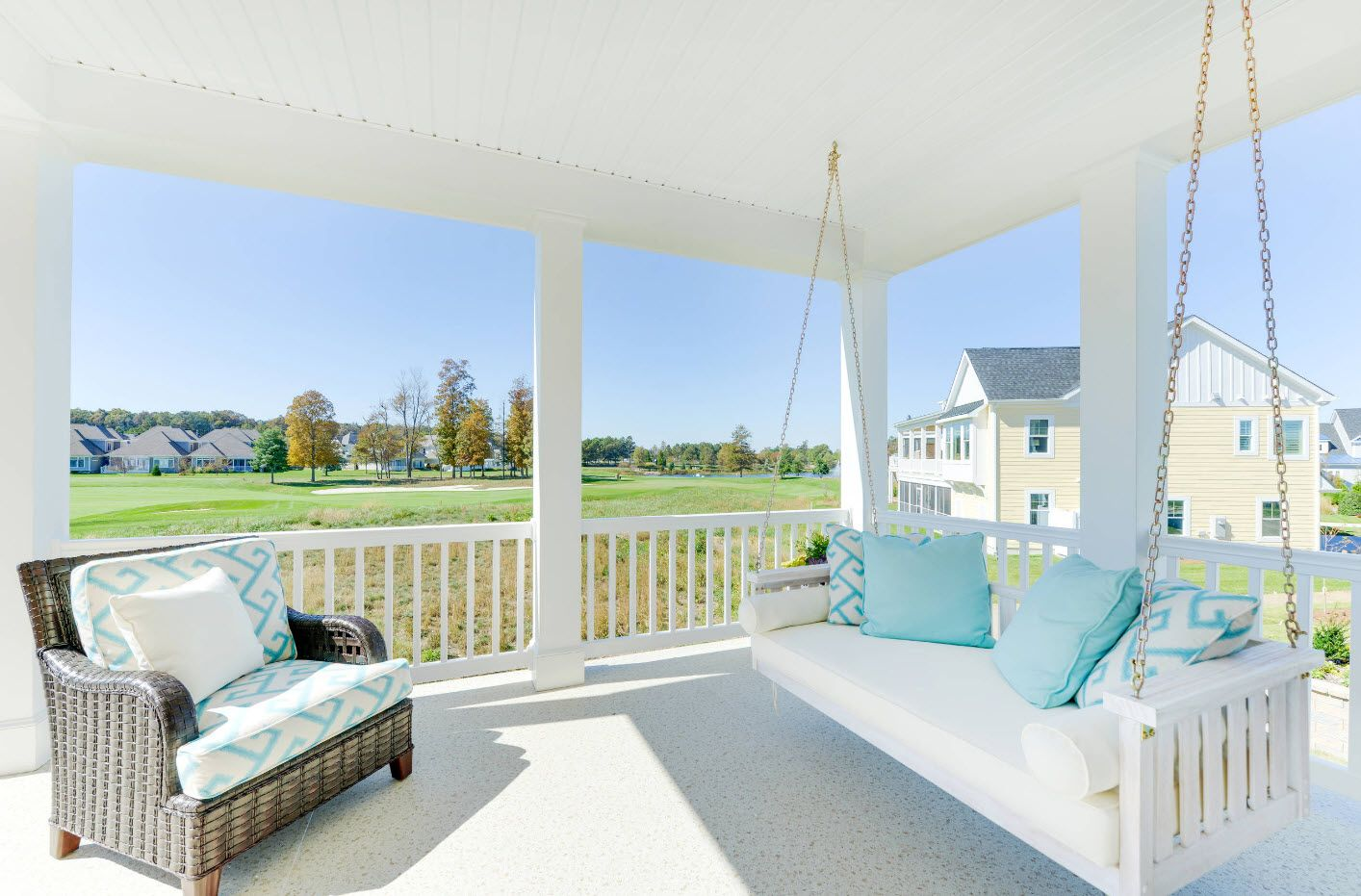 Swing bed on the rope at the speckless white deocrated porch