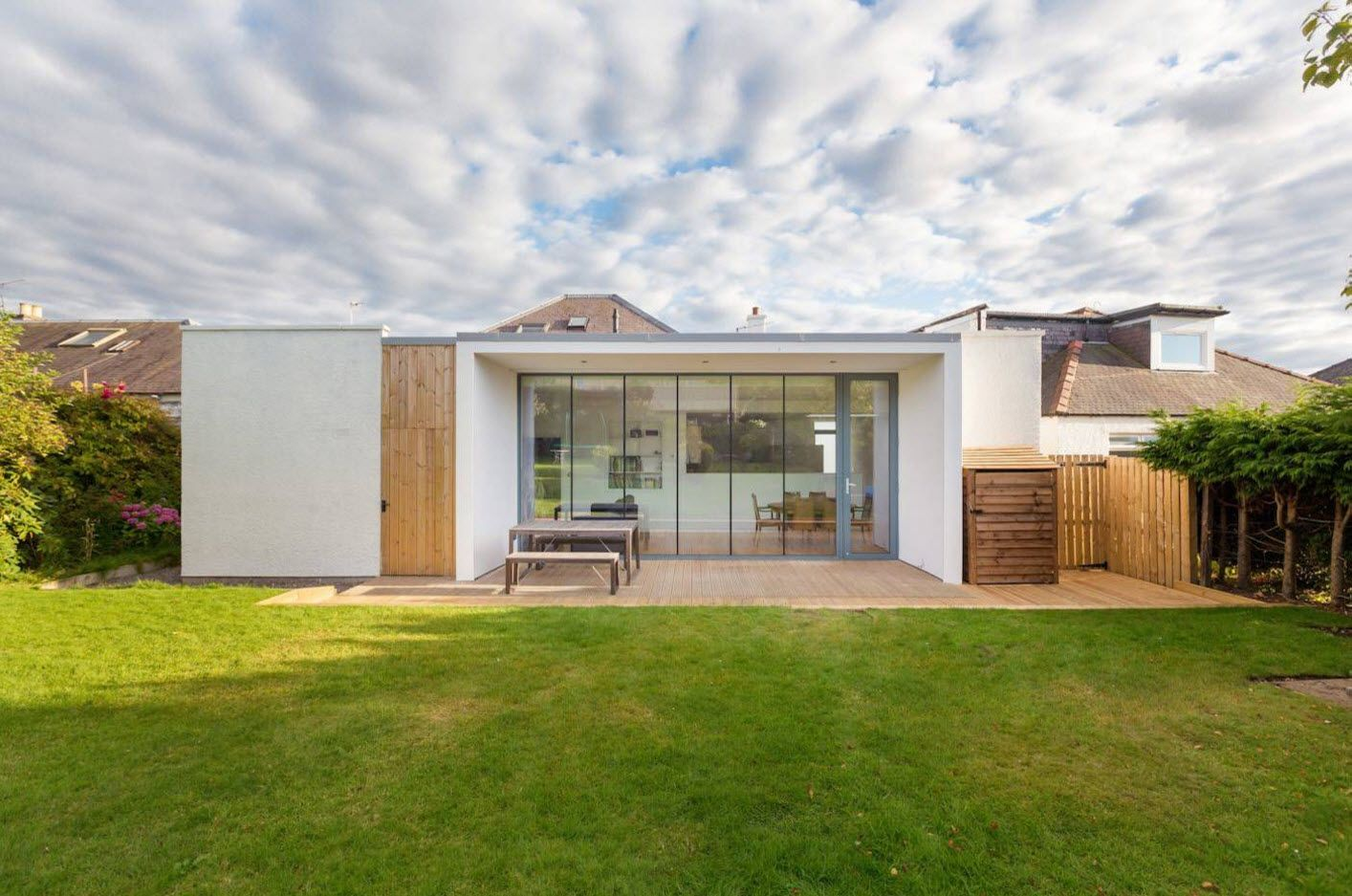 Gorgeous boxed cottage with concreted porch and green lawn in front of it