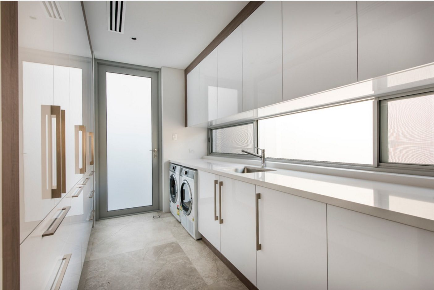 White and light gray play of tones for the narrow functional laundry room in the large orivate house