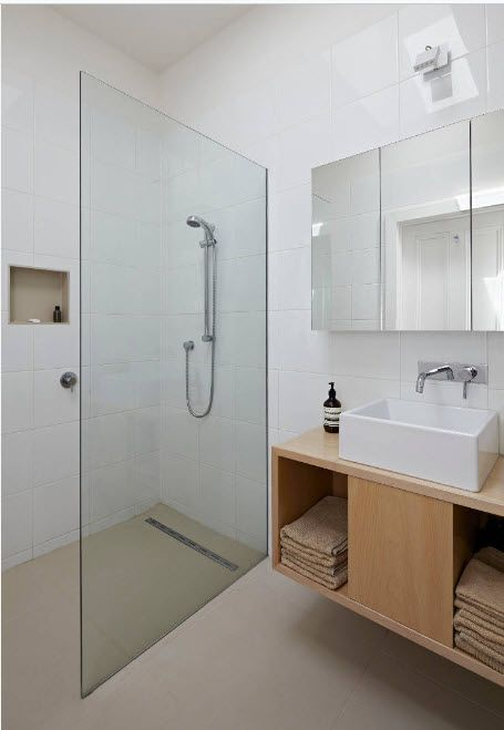 Minimalistic setting in the modern bathroom with glass separated shower zone