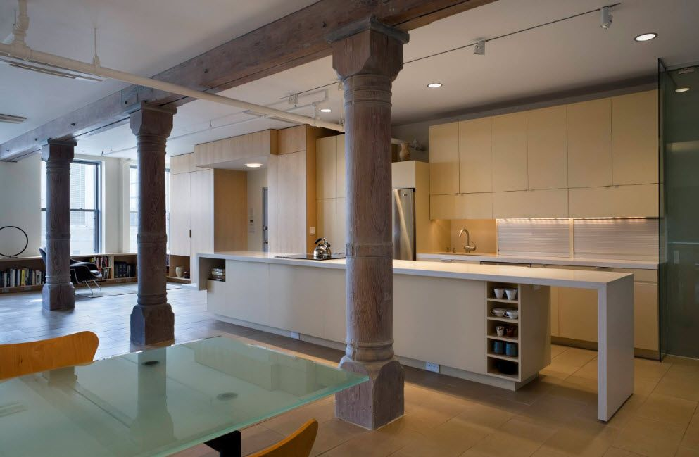 Grandeur colonnade of wooden columns in the loft kitchen with glass table