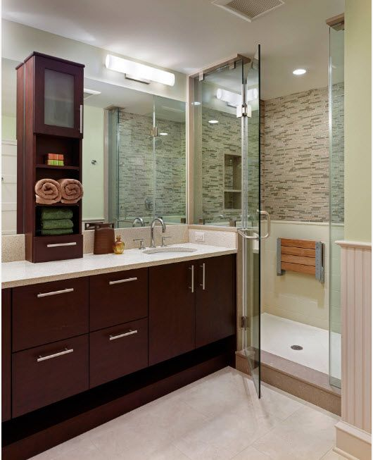 Dark wooden vanity and stone tiled walls for small functional bathroom with shower zone