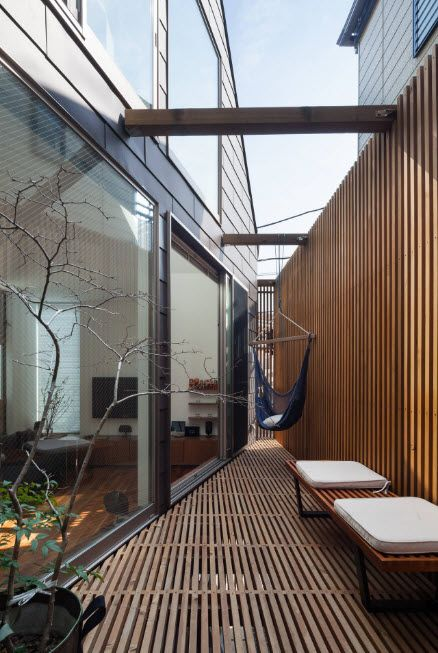 Open layout and glass walls for hi-tech styled private house and teh hammock between it and the blind wooden fence