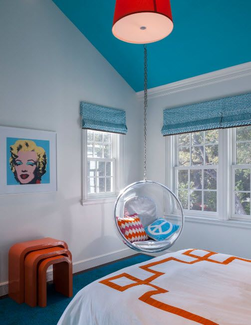 Private house's kids room with blue selective decorative elements and plastic translucent suspended chair