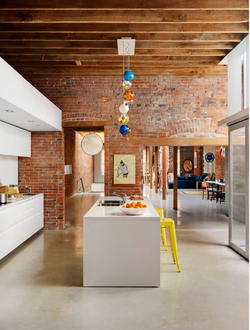 Brickwork and colorful lamps for the perky loft kitchen with multileveled white furniture set