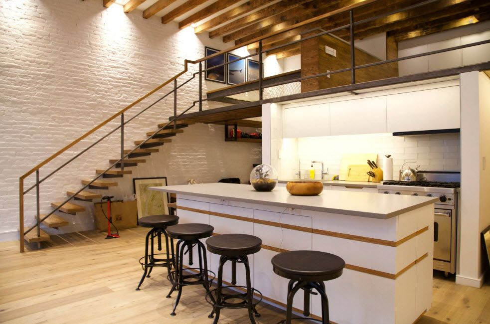 Large space of the loft kitchen with black round tables, latticed ceiling and stairway to the second level
