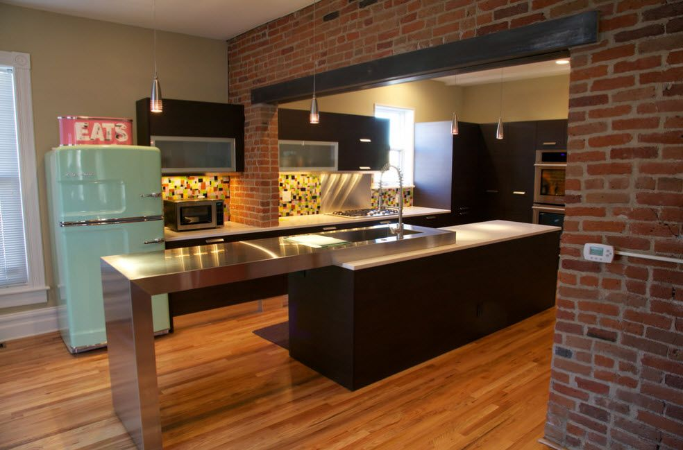 Large space for the dark finished kitchen with noble wooden laminate and dark island in the center