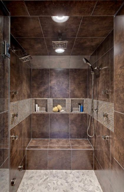 Totally trimmed with dark marble shower cabin with small shelving inside the wall