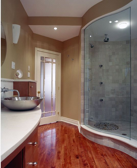 Wavy architectural features if the bathroom with stone tile finished glass cabin