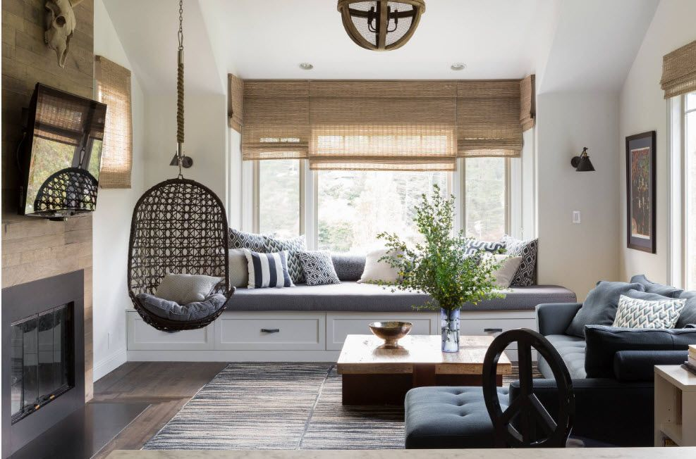 Dark rattan wicker suspended chair and Roman blinds of same material for eco styled living