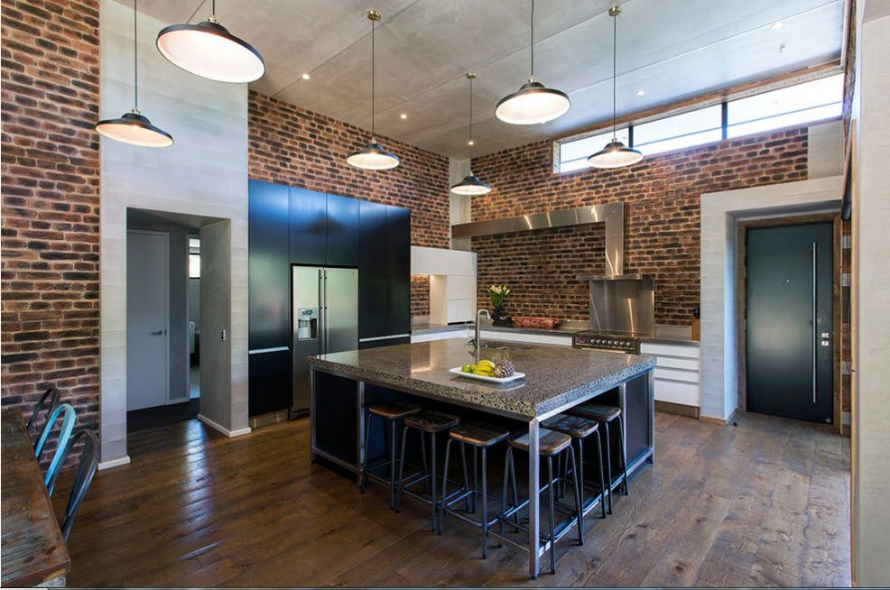 Hollow centered kitchen island in the dark brickwork finished kitchen with industrial hanging lamps