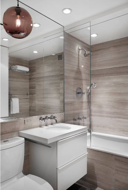 Solid stone tile in gray color scheme for the modern decorated bathroom with large mirror