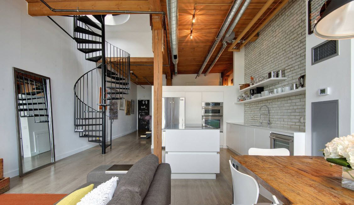 Spiral metal stairs and the wooden finished ceiling at the matted white loft kitchen