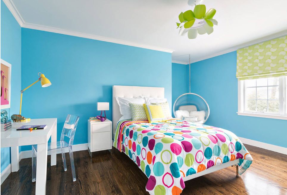 Bright kids' room design of azure painted walls and a blanket with colorful circles