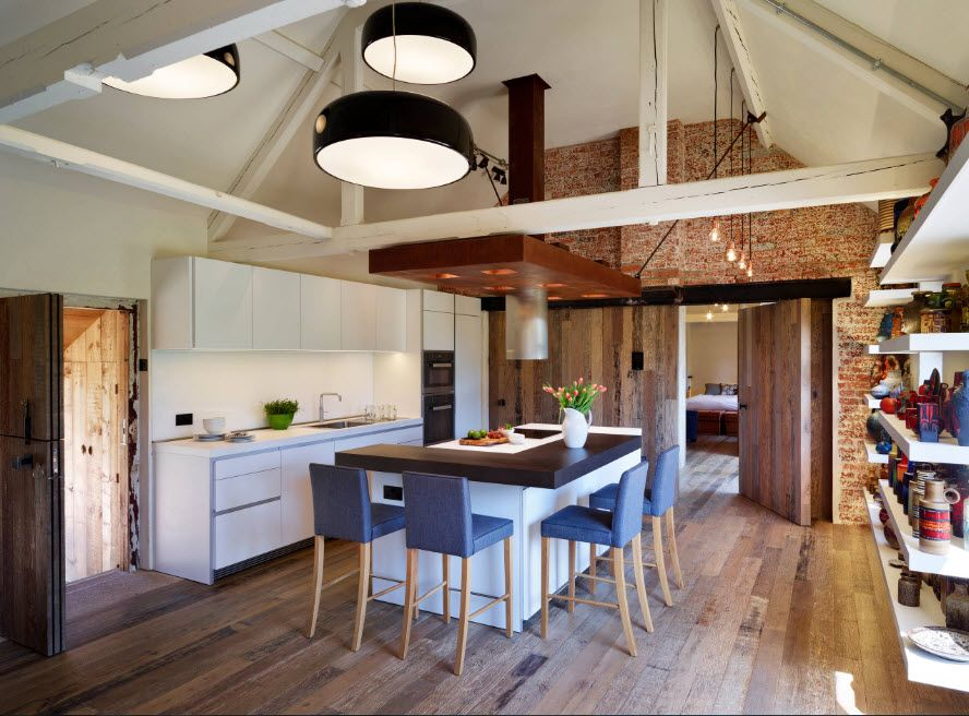 Square loft kitchen high ceiling with open beams and construction, large lamps with black shades and light-wooden laminate
