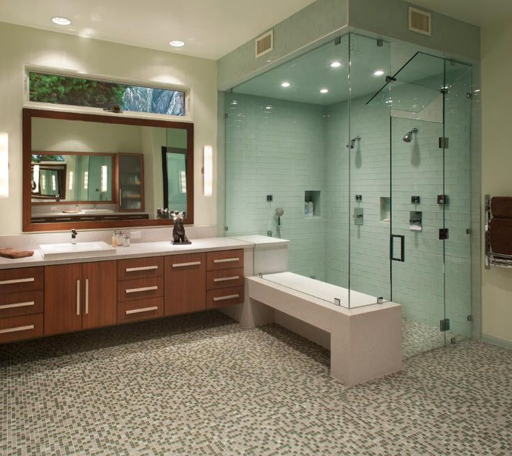 Spacious nicely decorated bathroom with mosaic at the floor and azure cabin zone with black plumbing