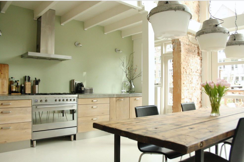 Olive wall paint and the open matted ceiling beams in the loft kitchen interior