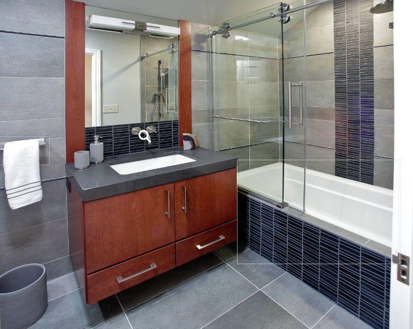 Dark wooden vanity and dark blue tile