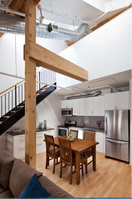 Lot of wooden materials and steel shining surfaces at the loft two-level kitchen