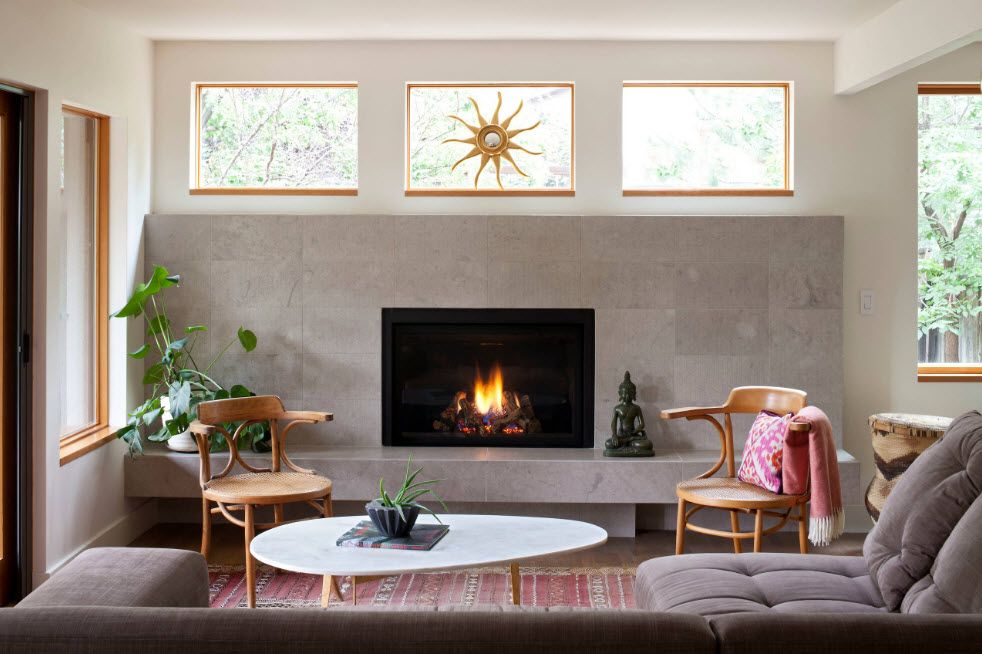 Artificial Fireplace as Part of Comfortable Life. Modern gray matted wall finishing with three glass windows and the starburst mirror