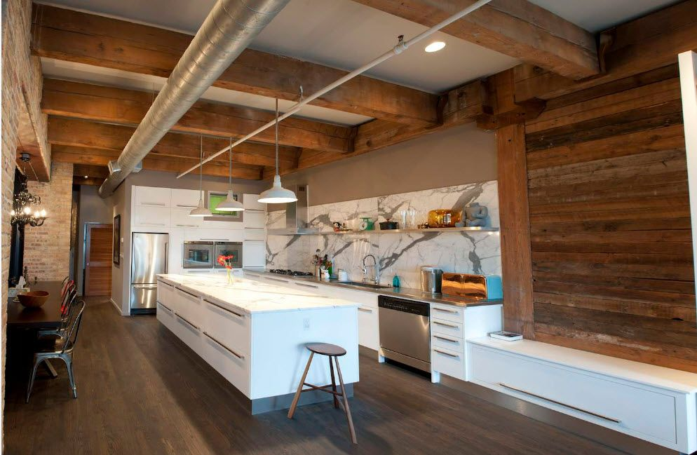 Open ceiling beams and the large white kitchen island in the center