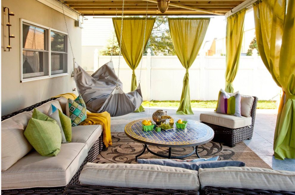 Outdoor patio with lime curtains and hanging armchair