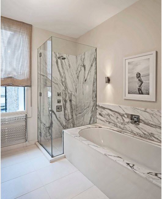 Gorgeous white with dark straks marble finishing of the shower zones of the bathroom