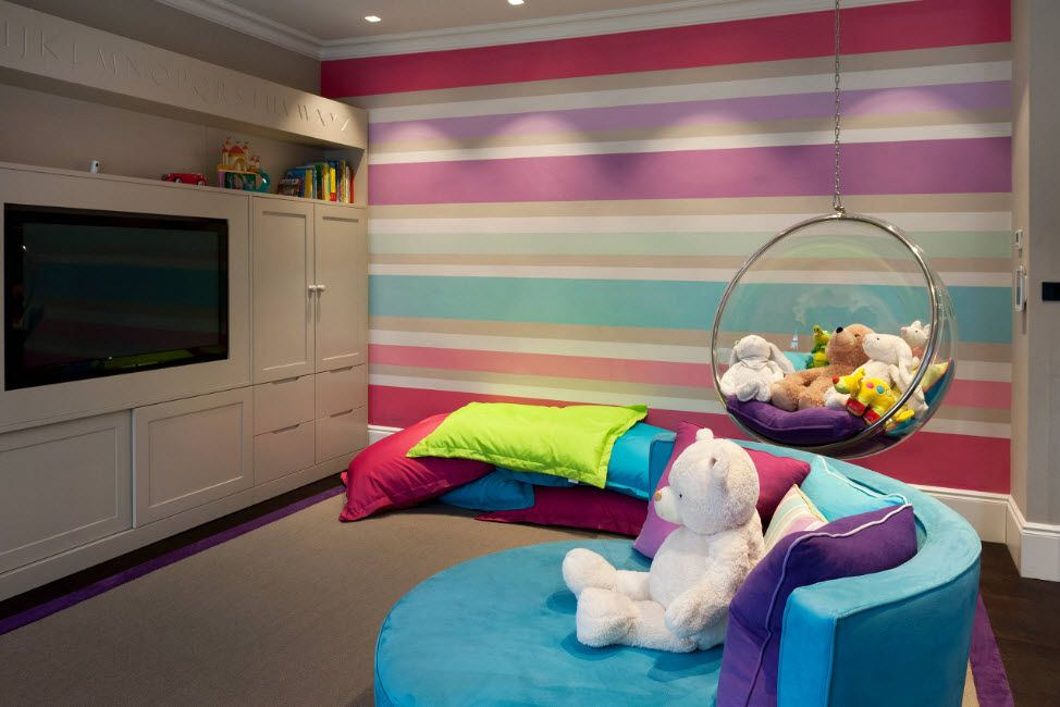 Rainbow-like painted wall in the kids room with a pile of colorful pillows and modular chest