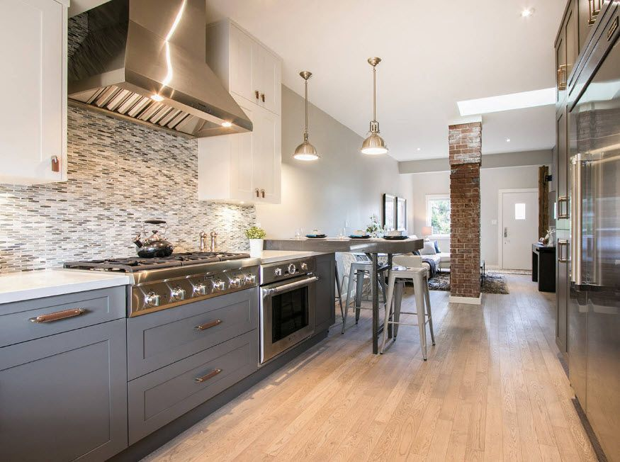 Steel surfaces of the hood and oven perfectly combine with gray colored furniture set