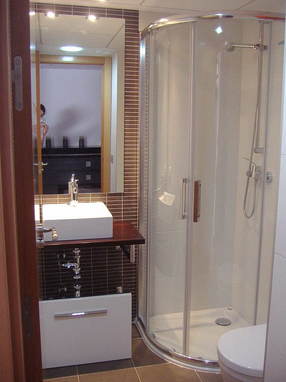 Modern Bathroom Interior Shower Cabin Design. Open plumbing and layout of the bathroom with black tike finished vanity