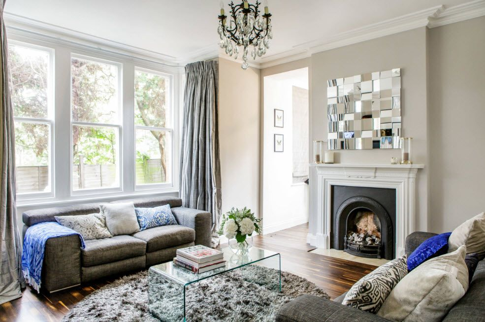 Artificial Fireplace as Part of Comfortable Life. Classic interior with large window and decorative installation above the hearth