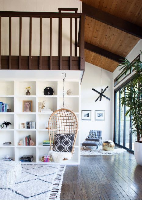 Two-level apartment with large white painted shelving and suspended chair