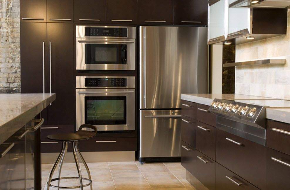 Loft Styled Kitchen. Industrial Motiffs for Comfortable Life. Steel surfaces of the appliances and dark brown furniture set