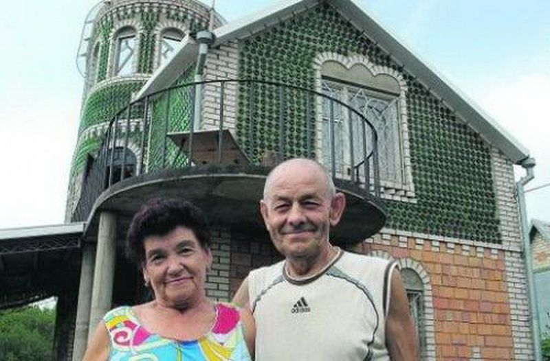 Unique Designed DIY House Built of Bottles. The overall view out of the fence. Enterprising and hardworking house owner with his wife