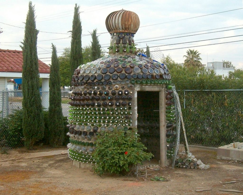 Unique Designed DIY House Built of Bottles. The overall view out of the fence. The outside shower built of the same materials
