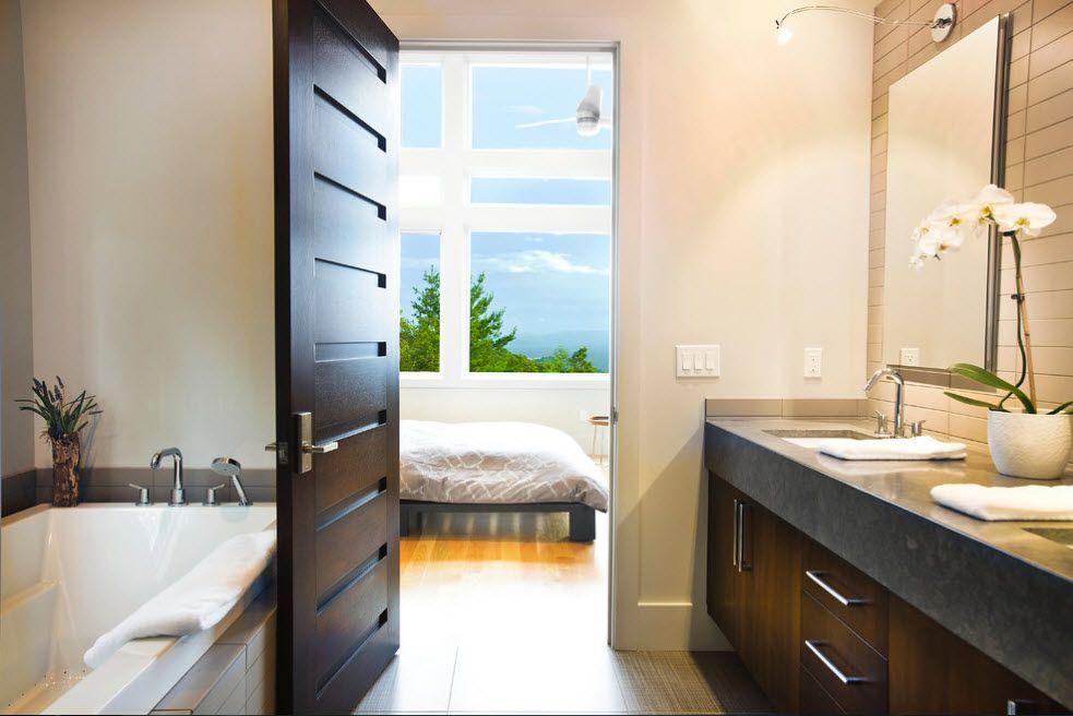 Dark wooden panels of the door and spectacular view to the sun lit bedroom