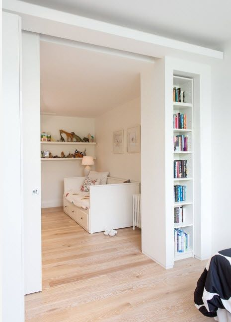 Sliding door frame in matted white paint and small improvised door niche with shelving