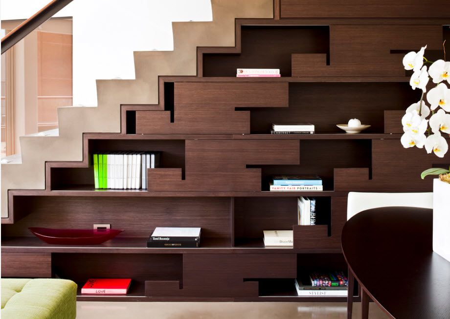 Shelving as Zoning Element & Storage for Modern Interior. Unusual forms under the stairs