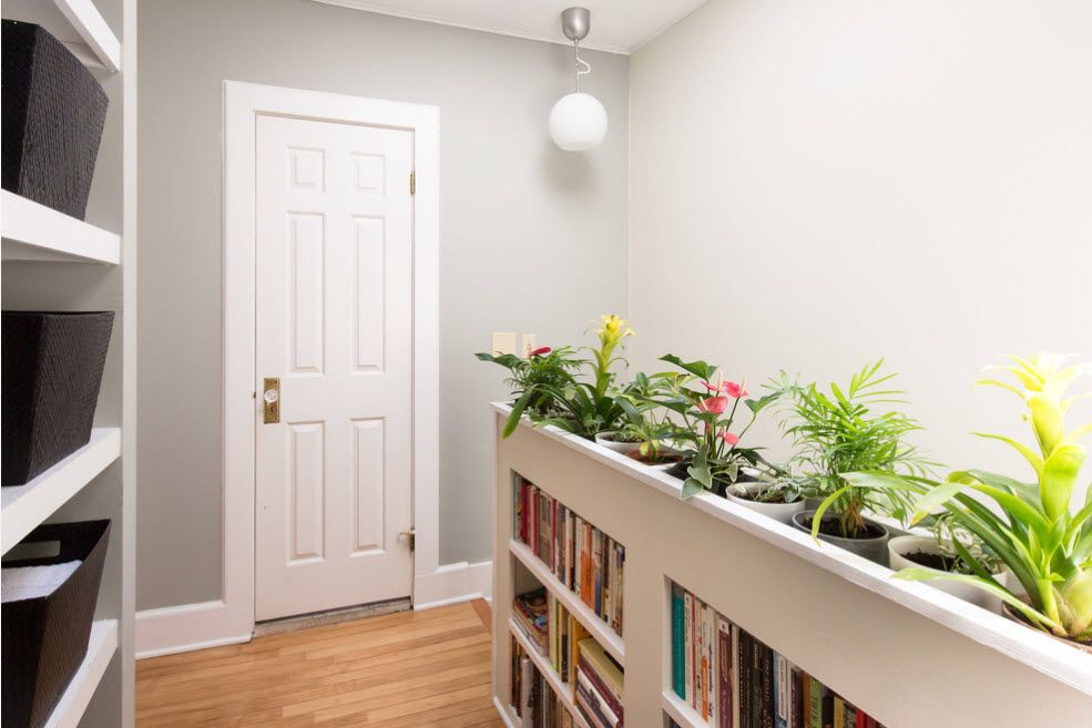 Shelving as Zoning Element & Storage for Modern Interior. Original decorating of the space near stairs with flower zone rigth at the top of the rack