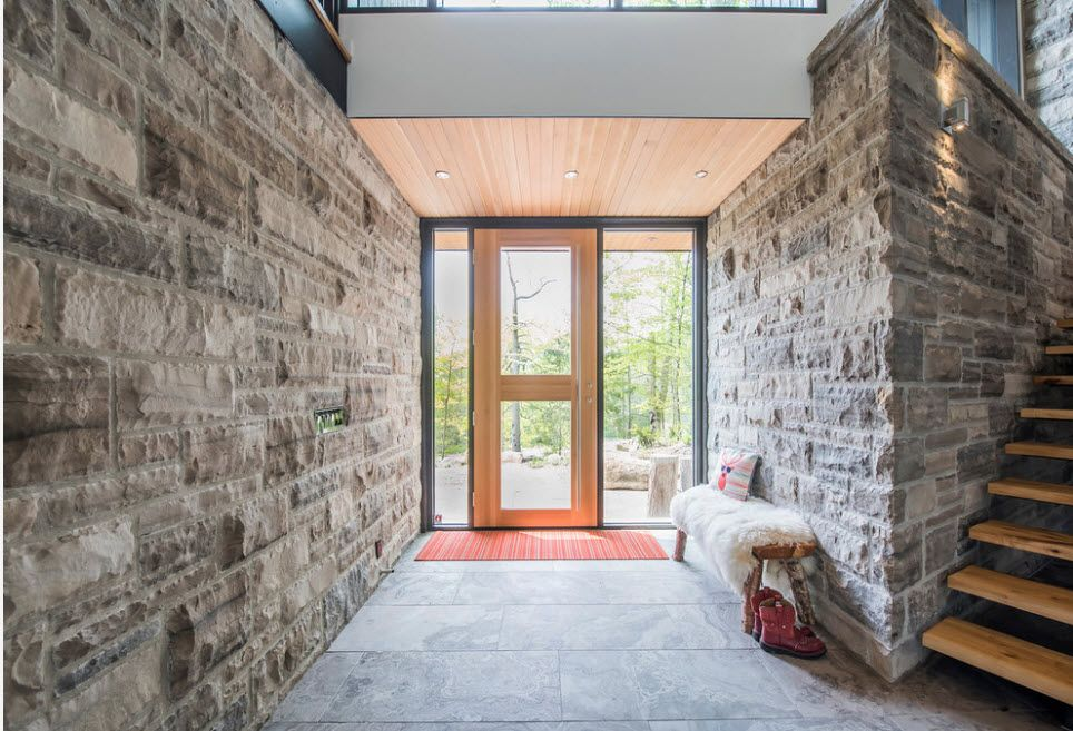 Full of light hall with panoramic wooden door and stone trimmed walls