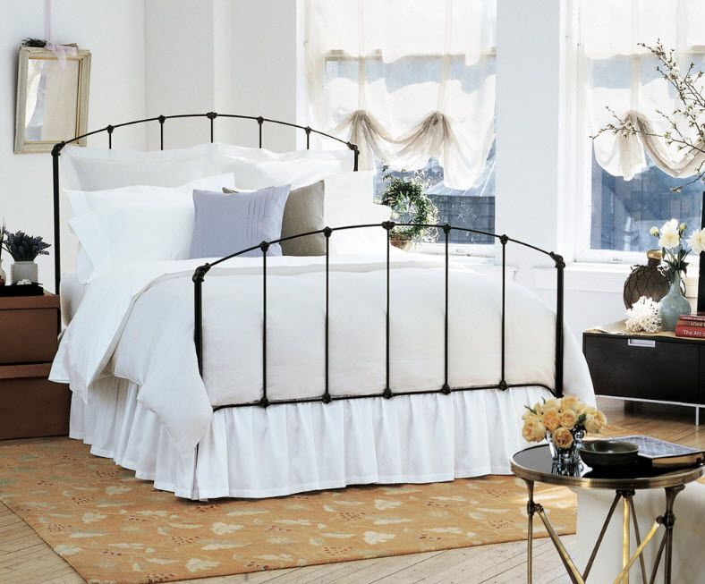 Wrought-iron Bed as a Stylish and Functional Interior Element. Unexpected as if hovering in air bed frame in black to emphasize white matress