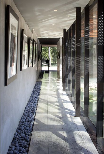 Pebble pathway right at the long hall of cottage with panoramic glass walls
