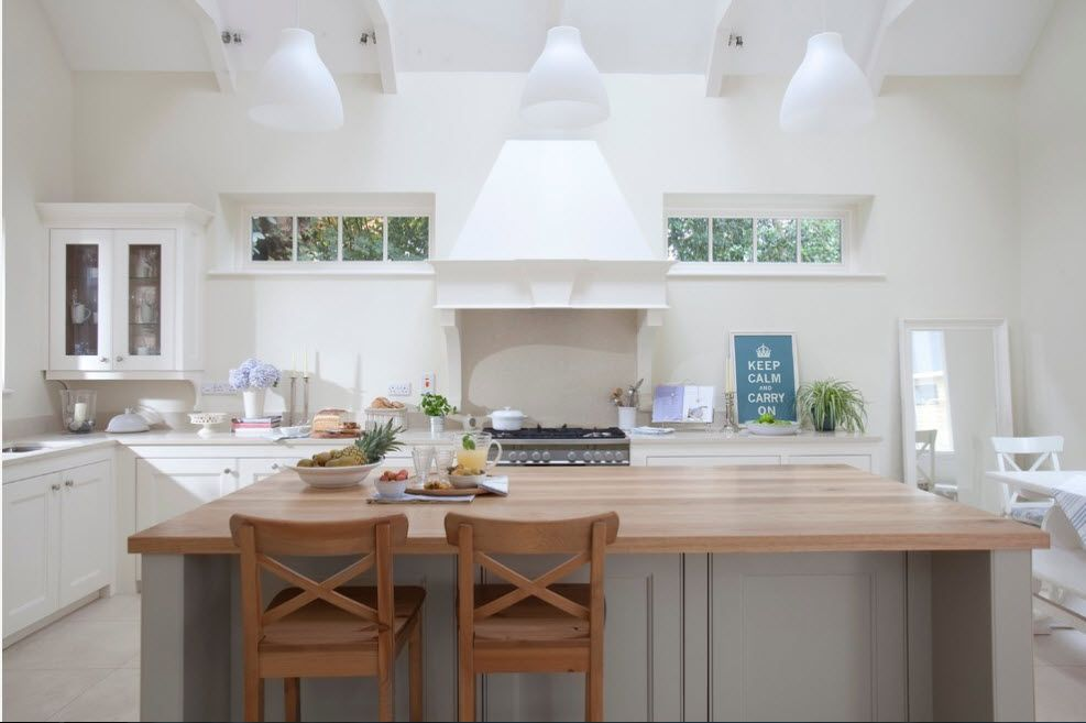 Light calming interior of the modern kitchen with big dome of the extractor hood and wooden furniture
